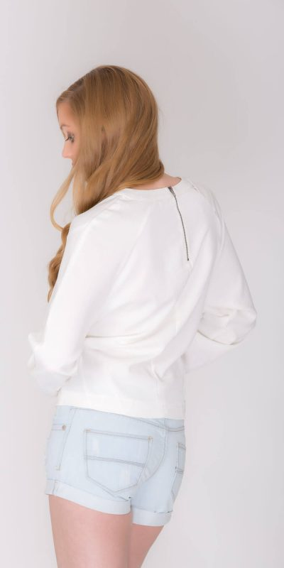 Fashion catalogue blond model wearing short jeans and white top. Back view.