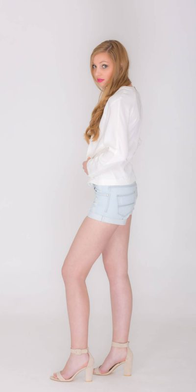Fashion catalogue blond model wearing short jeans and white top. Side view.