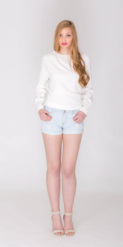 Fashion catalogue blond model wearing short jeans and white top.