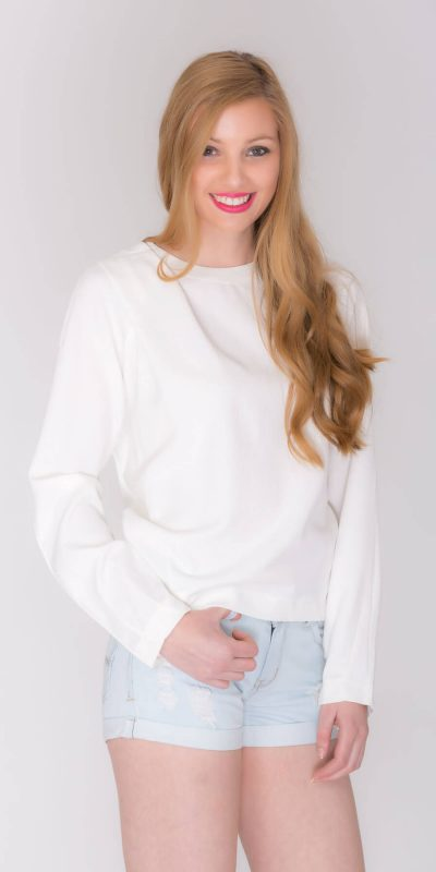 Fashion catalogue blond model wearing short jeans and white top. Close-up view.